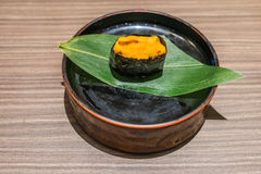 Uni Sushi Japanese food in black plate on wooden table Stock Photos