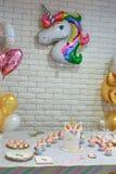 Unicorn party. Unicorn  balloon ,Kids birthday party decoration and cake. Decorated table for child birthday celebration. Rainbow unicorn cake Stock Photo