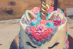 Unicorn birthday cake. For little girls decorated with colorful whipped cream and number nine on the top. Close up stock photos