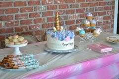 Unicorn Birthday Cake. Unicorn birthday table with cupcakes, macaroons, pretzel sticks. Blue, Pink, purple and gold colors royalty free stock image