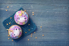Unicorn cupcakes. Above blue wooden background royalty free stock photo