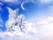 Unicorn with a fairy. Angel fairy on unicorn over a winter background stock photo