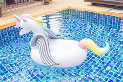 Unicorn flotation device. In swimming pool stock photography