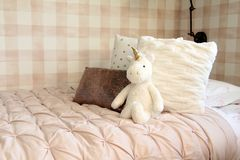 Unicorn on a girl`s bed. Unicorn stuffed toy leaning against bed cushions in a girls bedroom with plaid wallpaper royalty free stock images