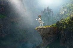 Fantasy Unicorn, Medieval Stone Castle. A unicorn horse is rearing up on a cliff ledge in a fantasy background with an old stone medieval castle. Castle royalty free stock image