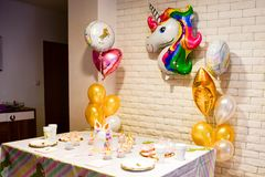 Unicorn for a party. Unicorn balloon ,Kids birthday party decoration and cake. Decorated table for child birthday celebration. Rainbow unicorn cake royalty free stock images