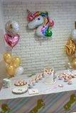Unicorn for a party. Unicorn  balloon ,Kids birthday party decoration and cake. Decorated table for child birthday celebration. Rainbow unicorn cake Royalty Free Stock Photography