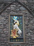 Unicorn of Scotland and red lion rampant, EDINBURGH, SCOTLAND. Unicorn of Scotland and red lion rampant on the medieval scottish stone wall in summer day Stock Photo