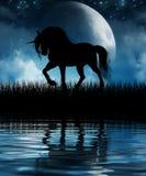 Unicorn Silhouetted mágico contra a lua fotografia de stock