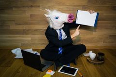 Unicorn in a suit and tie smiles and shows his finger on a a white empty sheet with copy space. Young man in rubber funny mask sits on the floor against a wall Stock Images