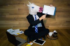 Unicorn in a suit and tie smiles and shows a white empty sheet with copy space. Young man in rubber mask sits on the floor against a wall and works with laptop Stock Images