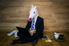 Unicorn in a suit and tie smiles and using laptop and gadgets on wooden background. Young man in funny rubber mask sits on the floor against a wall and works at Stock Photography