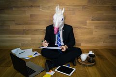Unicorn in a suit and tie using laptop and gadgets. Young man wearing rubber mask sits on the floor against a wall draws a graph Stock Image