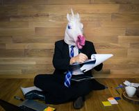 Unicorn in a suit and tie on wooden background in home office works with the documents. Young man in funny rubber mask sits on the floor against a wall and royalty free stock photos
