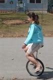 Unicycle adolescente joven del montar a caballo de la mujer abajo de una calle residencial Foto de archivo