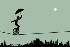 Unicycle on tightrope wire. Person riding a unicycle and balancing it with an umbrella going through a tightrope rope with cityscape silhouette at the background Royalty Free Stock Photography