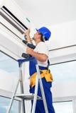 Unidad de aire acondicionado del montaje del trabajador Fotografía de archivo libre de regalías
