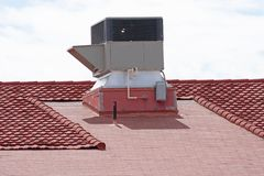 Unidad de aire acondicionado en un tejado de teja de la arcilla roja de un edificio foto de archivo