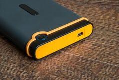 Unidad de disco duro externa en fondo de madera foto de archivo