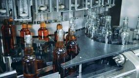Unidad de la cervecería con las botellas de relleno de un mecanismo con alcohol metrajes