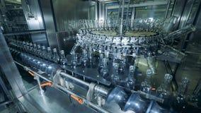 Unidad de la destilería con las botellas de cristal que se mueven a lo largo del transportador almacen de metraje de vídeo