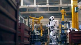 Unidad de la fábrica con el equipo industrial y un droid almacen de video