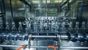 Unidad de la fábrica con las botellas de cristal que consiguen llevadas por una máquina del metal almacen de metraje de vídeo