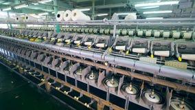 Unidad de la fábrica de la ropa con los carretes que consiguen la herida en una fábrica de la materia textil metrajes