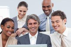 Unidad de negocio Multi-ethnic sonriente que usa una computadora portátil Foto de archivo