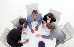 Unidad de negocio que se sienta alrededor de una conferencia Imagen de archivo