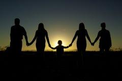 Unidad y unidad de la familia en puesta del sol Foto de archivo