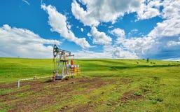 Unidade de bombeamento para o óleo de bombeamento em um prado verde contra um céu azul com as nuvens no verão Fotos de Stock