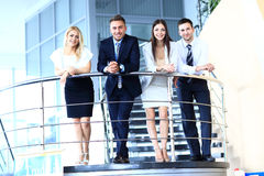Unidade de negócio positiva que está em escadas do escritório moderno imagens de stock