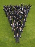 Unidade de negócio que Cheering na formação do triângulo fotografia de stock