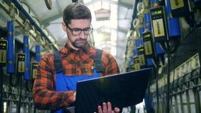 A unidade de ordenha industrial está obtendo inspecionada por um especialista com um portátil filme