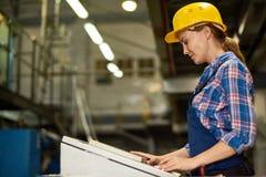 Unidades de máquina de funcionamiento de la mujer joven en la fábrica Imagen de archivo