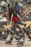 Unidendified kid are feeding pigeons with dry corn at Durbar Square in Bhaktapur, Nepal after major earthquake in 2015. Royalty Free Stock Images
