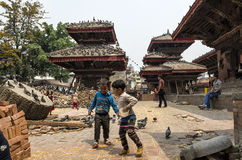 Unidendified kids are feeding pigeons with dry corn at Durbar Square in Bhaktapur, Nepal, after major earthquake in 2015. Stock Images
