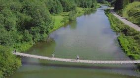 Unidenfied-Leute, die über die hängende lange Metallbrücke über Fluss gehen clip Familie auf der Brücke über dem Fluss stock video footage
