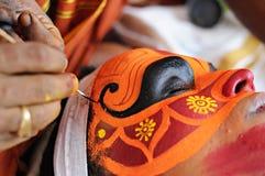 Unidenfied man som förbereder framsidamålningen för den Theyyam kapaciteten i Kannur, Indien November 28,2011 royaltyfri fotografi