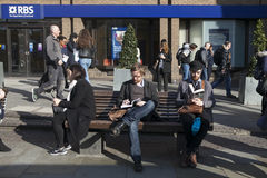 Unidentifed人在与游人的一条长凳读一本书在背景中 超过15百万人民每年访问伦敦 免版税图库摄影