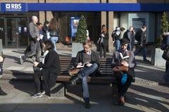 Unidentifed män läser en bok på en bänk med turister i bakgrund Mer än 15 miljon personer besöker London varje år Royaltyfri Fotografi