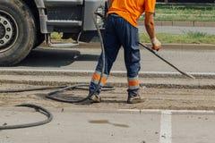 Unidentifiable arbetare för vägunderhåll som reparerar körbanan royaltyfria foton