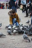 Unidentifiable child in Dam Square in Amsterdam besieged by pigeons on a winter day stock photos