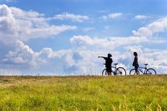 Unidentifiable cyklister på ängen, Tjeckien - kontur royaltyfria bilder