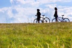 Unidentifiable cyklister på ängen, Tjeckien - kontur fotografering för bildbyråer