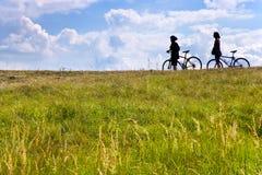 Unidentifiable cyklister på ängen, Tjeckien - kontur arkivbilder