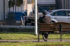 Unidentifiable ensamt gamal mansammanträde på en parkerabänk som röker ett rör royaltyfri fotografi