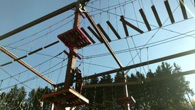 Unidentifiable family climbing in high rope park stock footage