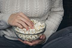 Girl holding glass bowl with popcorn. royalty free stock photos
